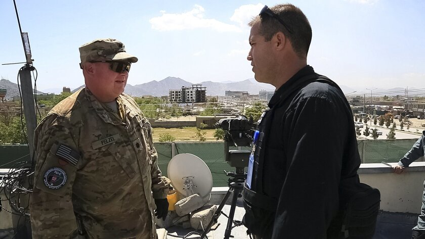 Col John Graham (right) updates Lt. Col. Ted Pelzel on the change of mission during a recent trip in Kabul as they stopped to meet with the Afghan Police.