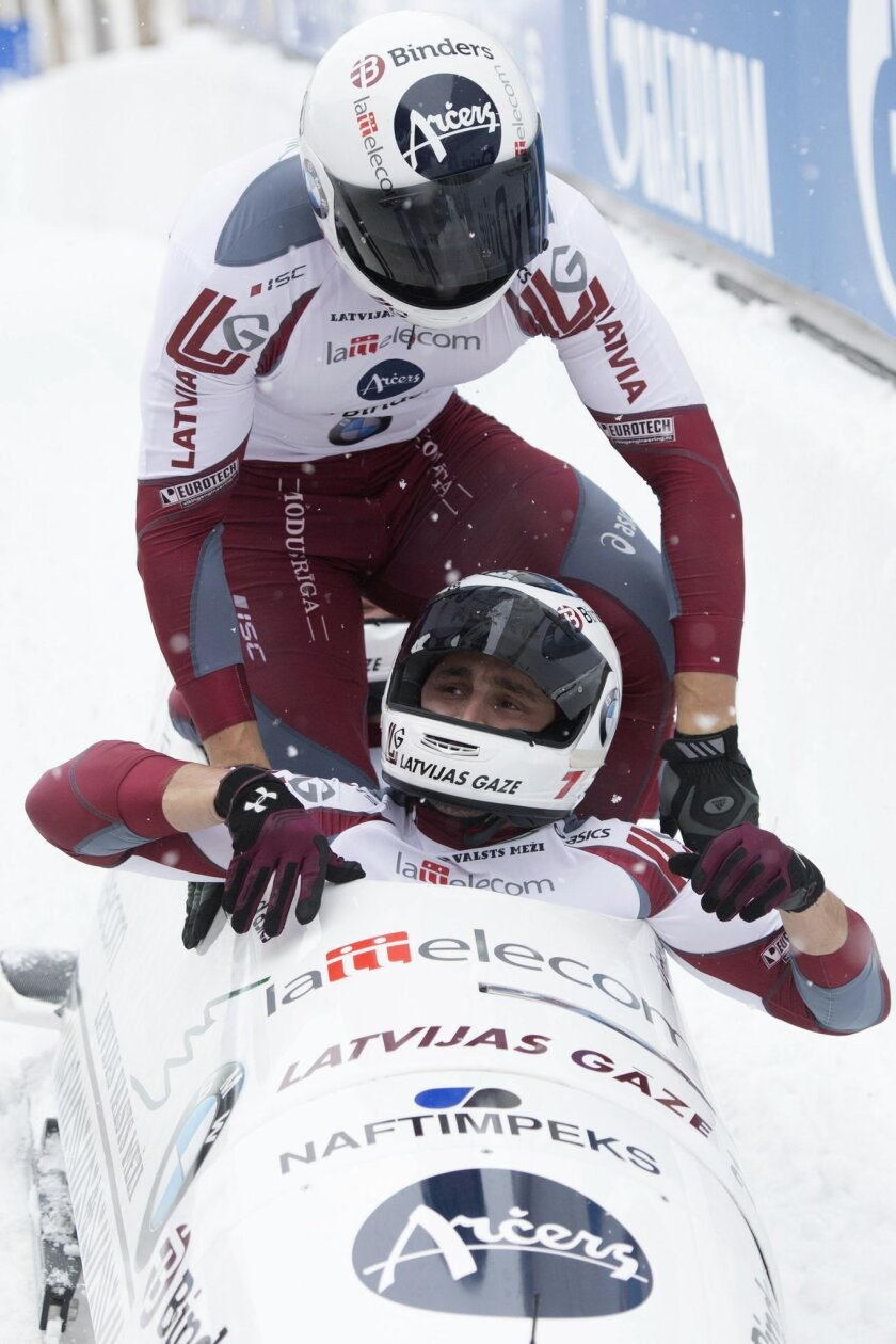 Latvia's Oskars Melbardis, Daumants Dreiskens, Arvis Vilkaste and Janis Strenga arrive in the finish area  after they placed third at the men's 4-man bobsled  World Cup competition in St. Moritz, Switzerland, Sunday, Feb. 7,  2016.  (Urs Flueeler/Keystone via AP)