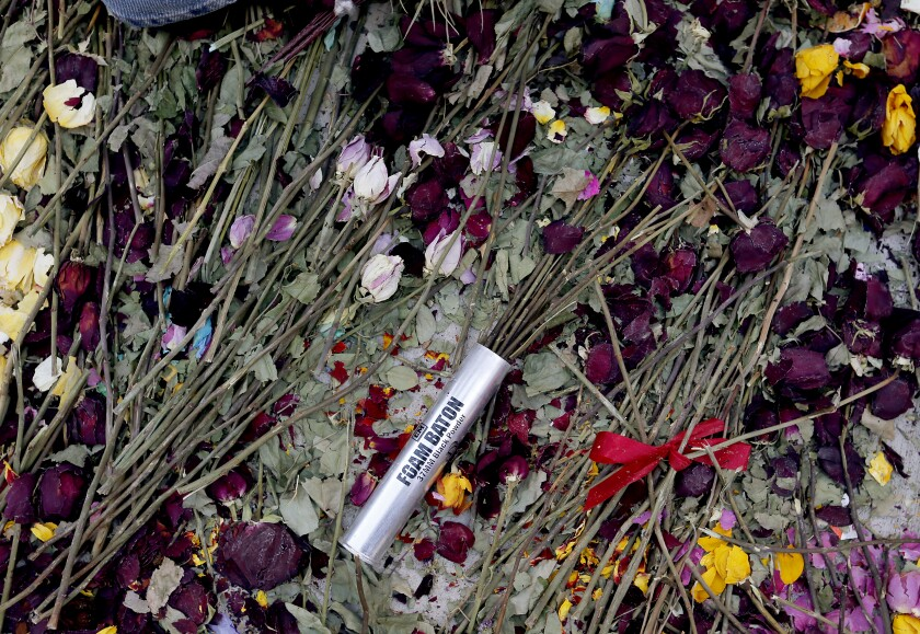 A shell casing serves as a vase for flowers amid a Black Lives Matter protest in downtown L.A.