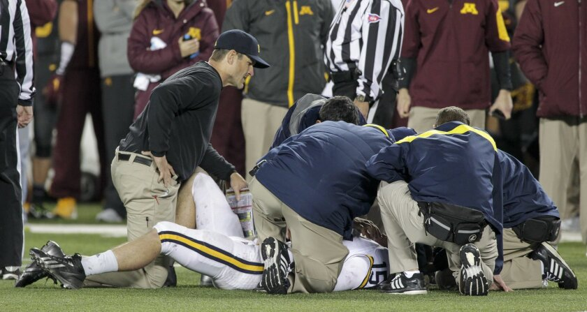 Michigan head coach Jim Harbaugh, left, looks on as staff checks on Michigan quarterback Jake Rudock (15) who left the game with an injuy during the second half of an NCAA college football game Saturday, Oct. 31, 2015, in Minneapolis.(AP Photo/Paul Battaglia)