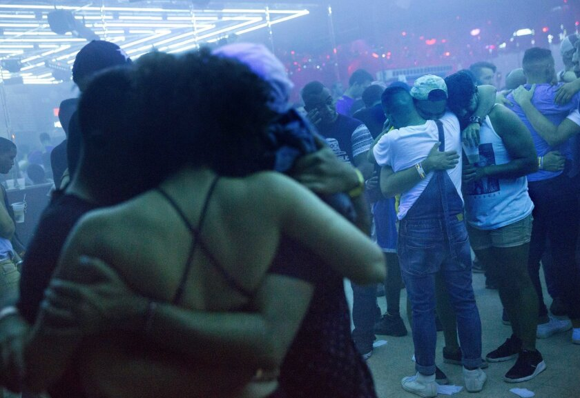 FILE - In this June 19, 2016, file photo, Club goers embrace at the approximate time one week ago that the Pulse nightclub mass shooting began as the music is turned off on the dance floor to observe a moment of silence at Parliament House, an LGBT nightclub early in Orlando, Fla. (AP Photo/David G
