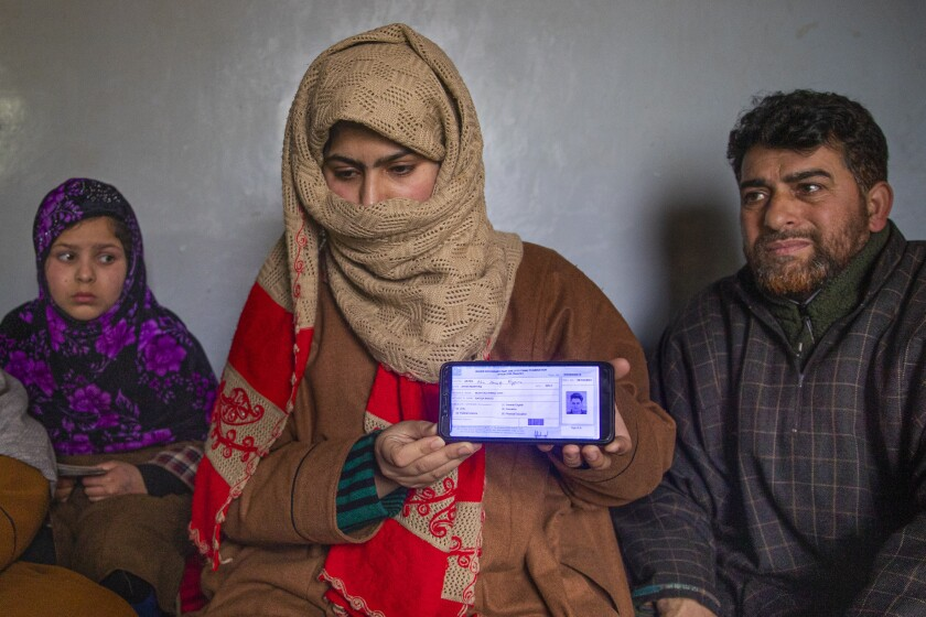 """Zarqa Mushtaq, center, shows on a mobile phone the 11th grade examination slip of her 16 -year old brother Athar Mushtaq, as her father Mushtaq Ahmad Wani, looks on while talking to the Associated Press in Bellow, south of Srinagar, Indian controlled Kashmir, Tuesday, Jan. 5, 2021. On the last week of 2020, Indian government forces killed Athar and two other young men during a controversial gunfight on the outskirts of the Indian-controlled Kashmir's main city. Police did not call them anti-India militants but """"hardcore associates of terrorists."""" They later buried them at a graveyard in a remote mountainous tourist resort miles away from their ancestral villages. Athar was the latest Kashmiri to be buried in a far-off graveyard after Indian authorities in a new controversial policy in 2020 started to consign blood-soaked bodies of scores of Kashmiri suspected rebels to unmarked graves, denying the mourning families a proper funeral and a burial. (AP Photo/ Dar Yasin)"""