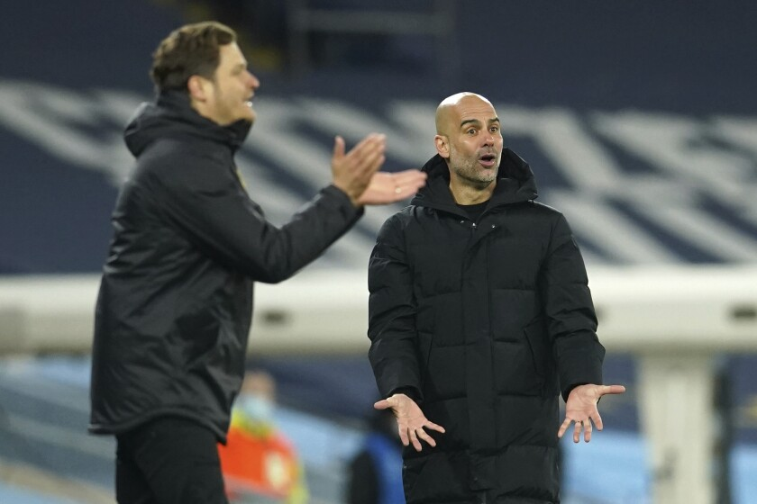 Manchester City's head coach Pep Guardiola, right, gestures during the Champions League, first leg, quarterfinal soccer match between Manchester City and Borussia Dortmund at the Etihad stadium in Manchester, Tuesday, April 6, 2021. (AP Photo/Dave Thompson)