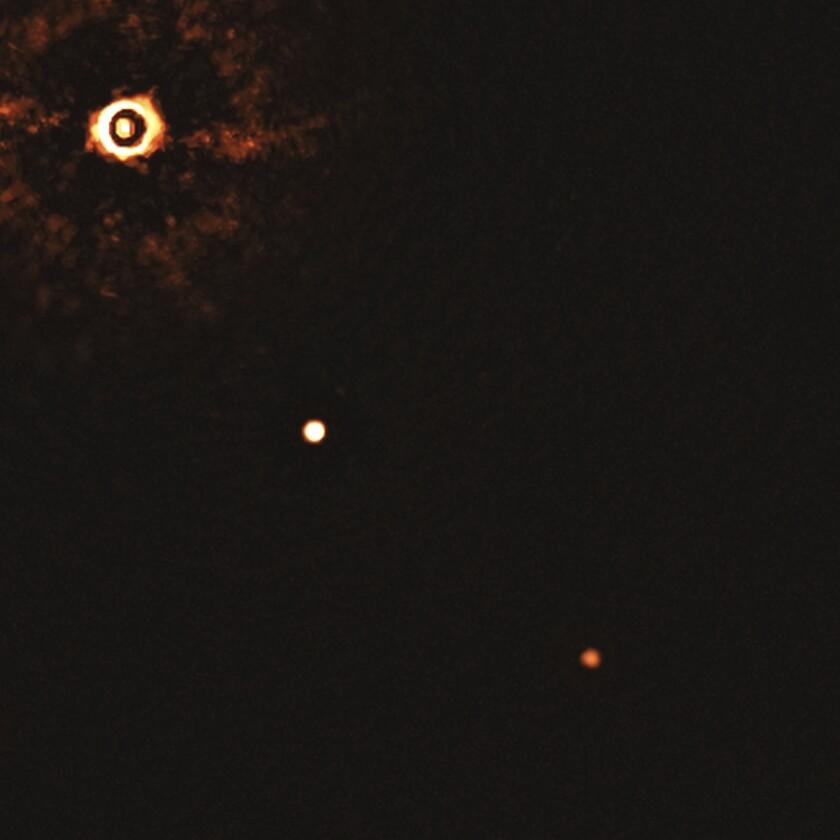 La estrella TYC 8998-760-1, superior izquierda, y dos exoplanetas gigantes.