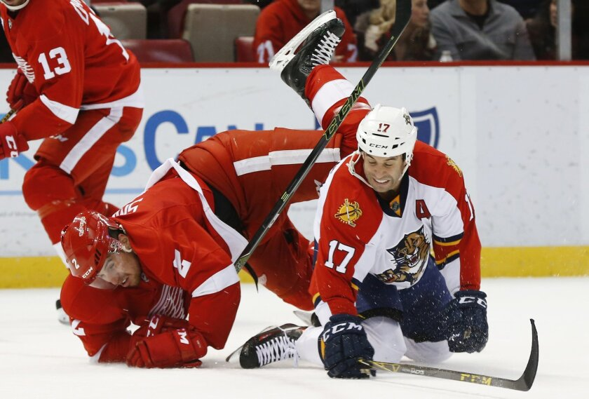 Detroit Red Wings defenseman Brendan Smith (2) and Florida Panthers center Derek MacKenzie (17) collide in the first period of an NHL hockey game, Monday, Feb. 8, 2016 in Detroit. (AP Photo/Paul Sancya)