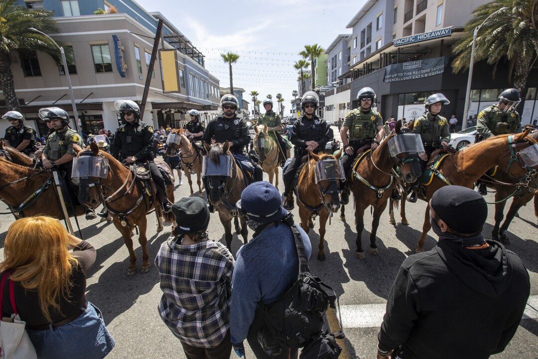 Protesters face a group of police officers on horseback