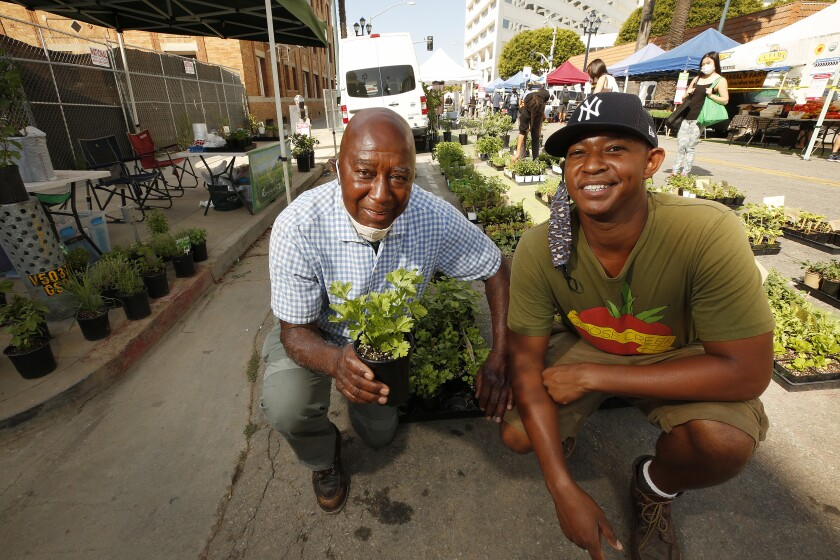 Black nursery owners Jimmy Williams, 79, and son Logan, 34,  smile and take a knee amid their seedlings.
