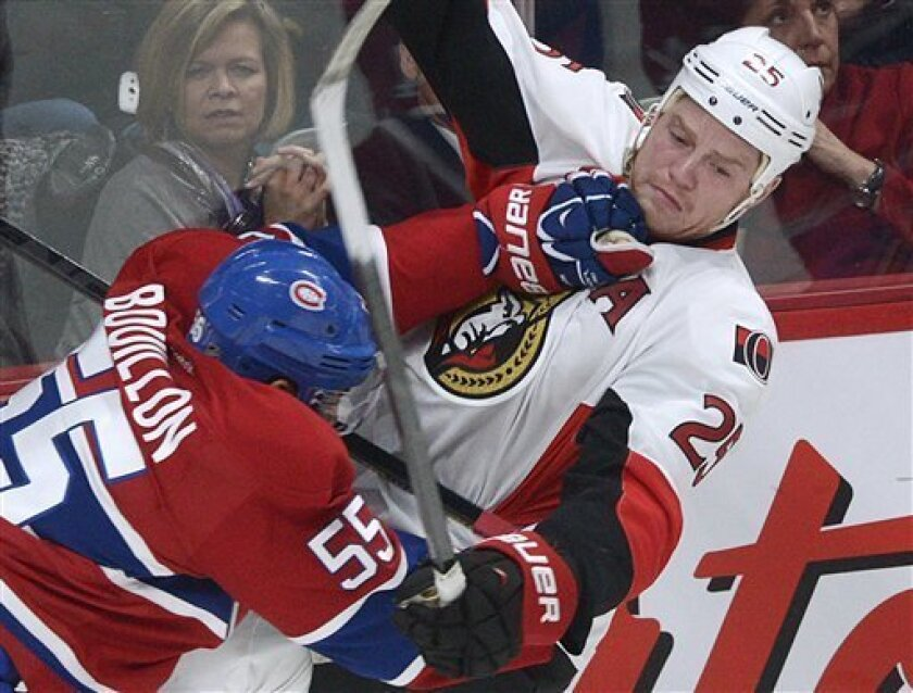 Montreal Canadiens' Francis Bouillon (55) collides with Ottawa Senators' Chris Neil during the second period of an NHL hockey game in Montreal, Wednesday, March 13, 2013. (AP Photo/The Canadian Press, Graham Hughes)