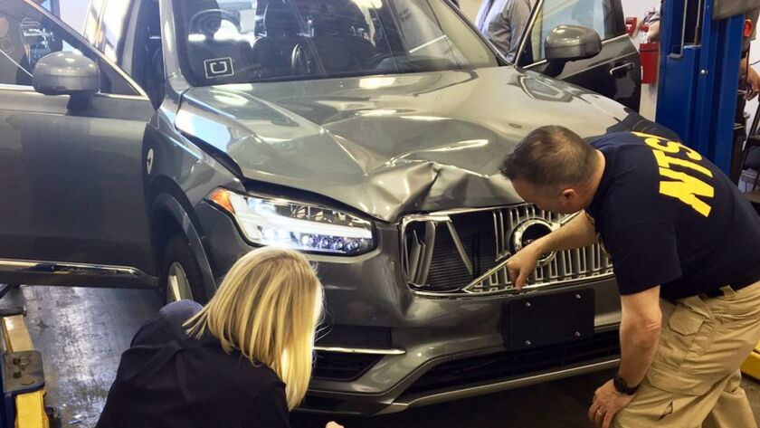 Investigators examine a driverless Uber SUV that fatally struck a woman in Tempe, Ariz.