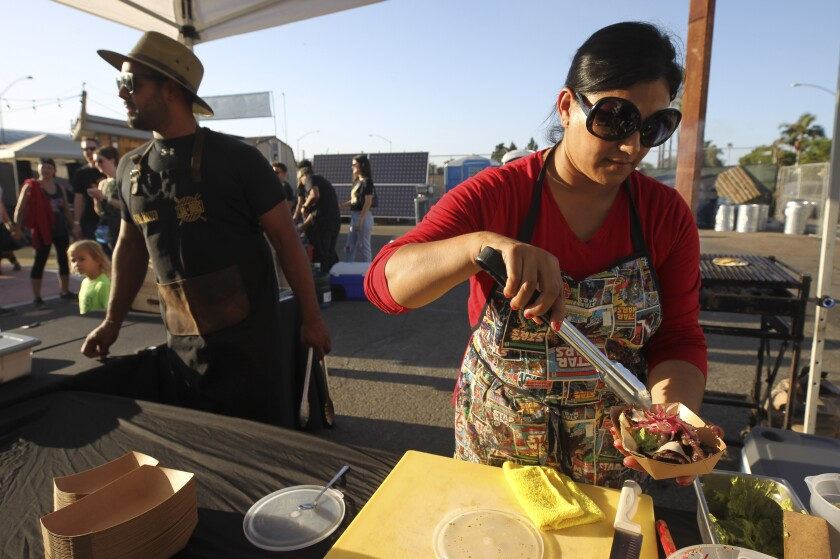 Claudia Toscano makes a taco during the City Heights Street Food Festival in 2019.