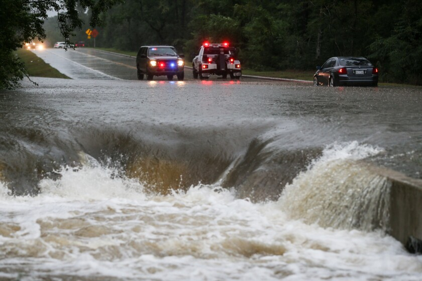 A police officer directs traffic away after a car is stranded in flash flooding on Friday in The Woodlands, Texas.