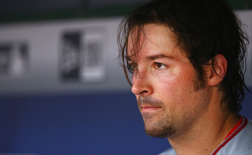Angels pitcher C.J. Wilson sits in the dugout during a July game against the Rangers in Arlington, Texas.