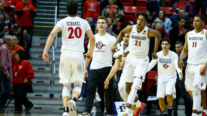 SDSU forward Malik Pope (21) runs onto the court to celebrate with guard Jordan Schakel (20) after their productive first half against Wyoming.
