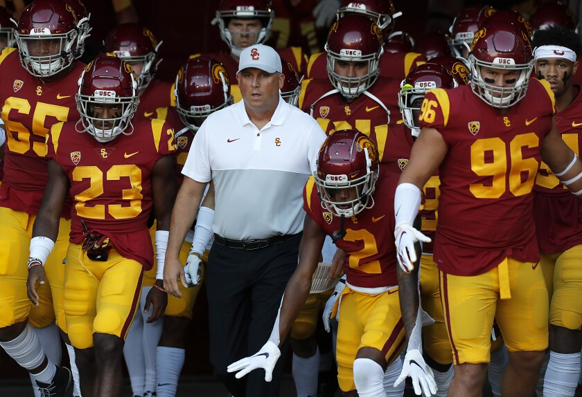 USC coach Clay Helton leads the Trojans onto the field at the Coliseum Sept. 20.