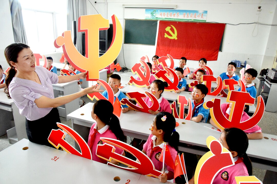 A woman holds a hammer and sickle emblem as children watch, holding their own red-and-gold emblems
