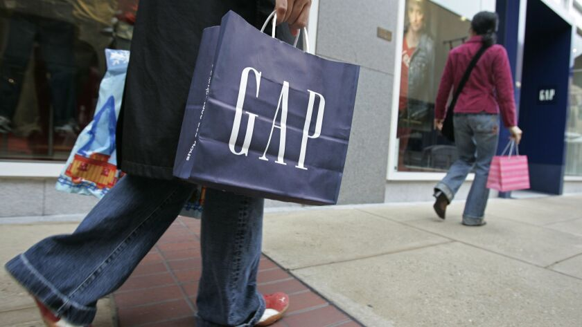 A shopper carries a bag from a Gap store.