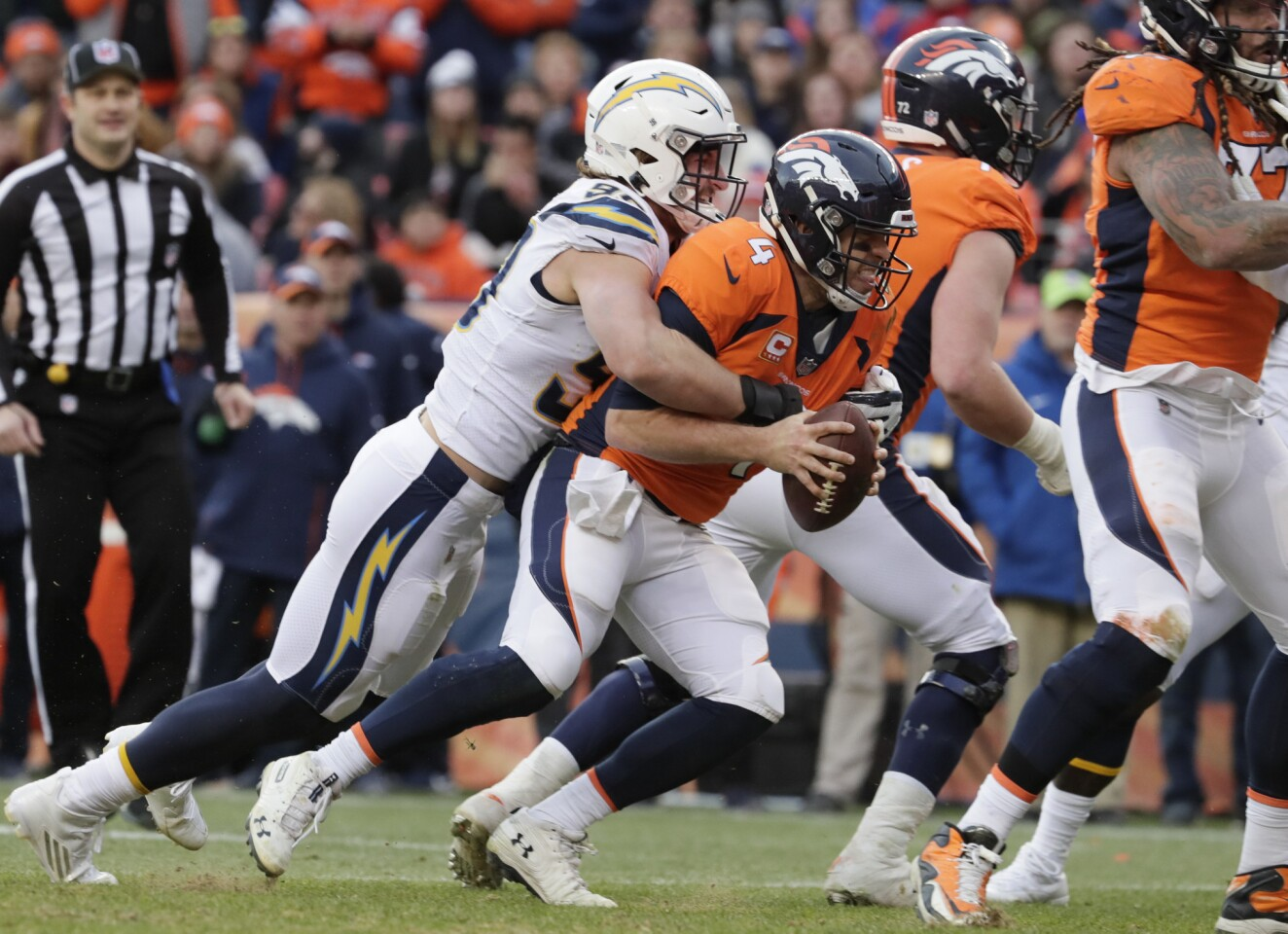 Chargers defensive end Joey Bosa sacks Broncos quarterback Case Keenum during a second quarter drive at Mile High Stadium.