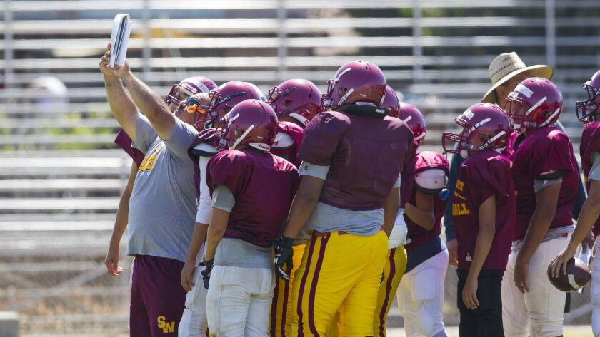 Southwest coach Paco Silva holds up his playbook for the offense to read before running a play.