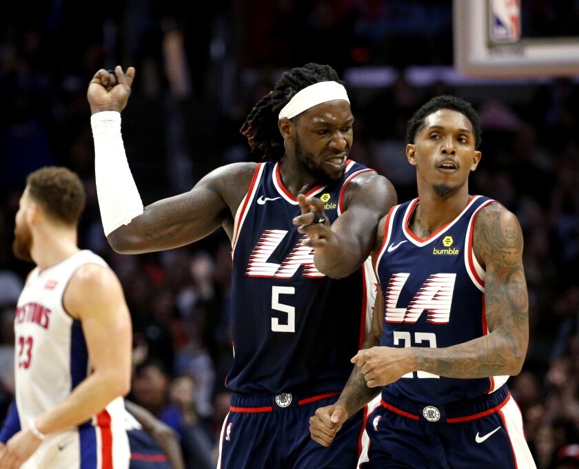 Clippers forward Montrezl Harrell, left, celebrates after Lou Williams, right, made a three-pointer against the Pistons on Jan. 12 at Staples Center.