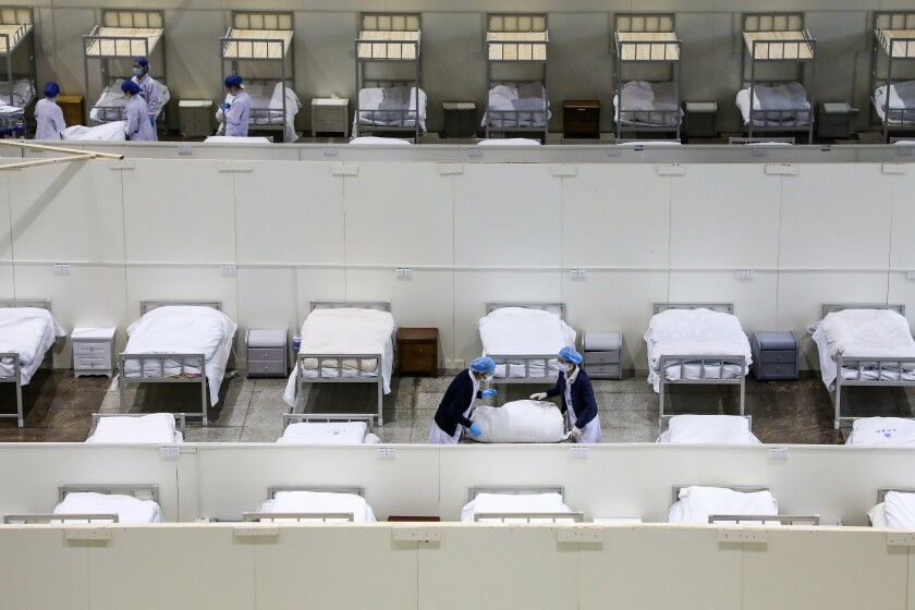 In this Wednesday, Feb. 5, 2020, photo, medical staff prepare beds at a temporary hospital which transformed from an exhibition center for accepting patients who diagnosed with the coronaviruses in Wuhan in central China's Hubei province. Ten more people were sickened with a new virus aboard one of two quarantined cruise ships with some 5,400 passengers and crew aboard, health officials in Japan said Thursday, as China reported 73 more deaths and announced that the first group of patients were expected to start taking a new antiviral drug. (Chinatopix via AP)