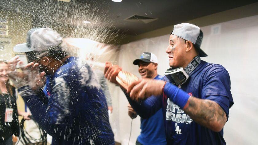 SAN FRANCISCO, SEPTEMBER 29, 2018-Dodgers Manny Machado sprays teamate Matt Kemp after clinching a p