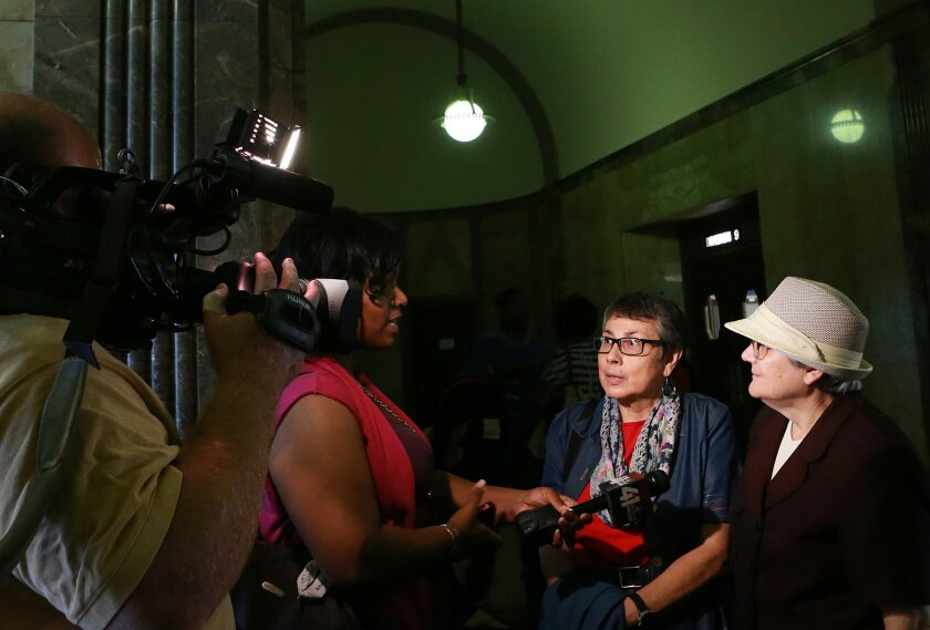 "FILE - In this Thursday, Sept. 25, 2014, file photo, same-sex couple Zuleyma Tang-Martinez, second from right, and Arlene Zarembka, right, of St. Louis, talk to news media in the Jackson County Courthouse in Kansas City, Mo. A judge struck down part of Missouri's gay marriage ban for the first time on Friday, Oct. 3, 2014, by ordering the state to recognize same-sex marriages legally performed in other states, saying state laws banning the unions single out gay couples ""for no logical reason."" The ruling was made in a lawsuit filed by 10 same-sex couples who legally married outside the state, including Zarembka and Tang-Martinez. (AP Photo/St. Louis Post-Dispatch, Christian Gooden, Pool, File)"