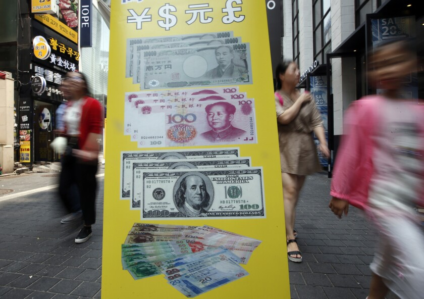 Visitors walk by signs displaying currency exchange rates at downtown Seoul, South Korea.