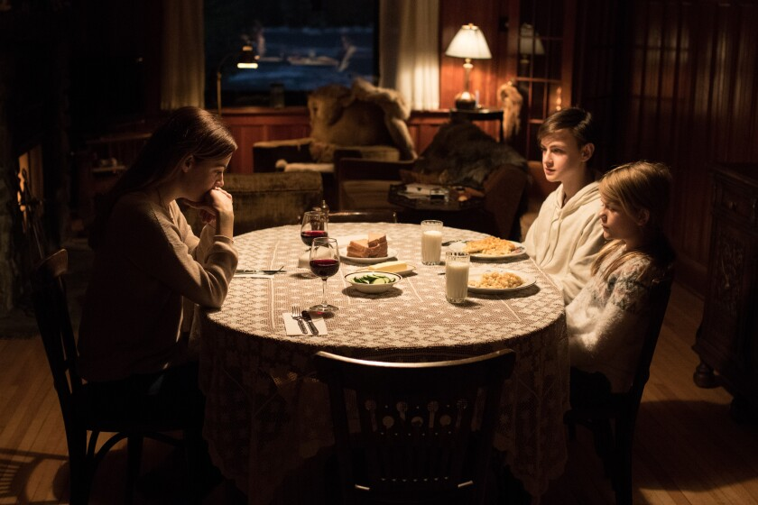 """Riley Keough, clockwise from left, Jaeden Martell and Lia McHugh in the movie """"The Lodge."""""""
