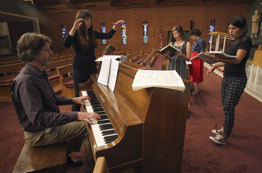"Pacific Lyric Association executive director Justin Gray plays piano while conductor Alexandra Keegan leads opera singers Caroline Nelms, second from right, and Camila Lima, who alternate in the role of Juliet, during a rehearsal of Charles Gounod's ""Romeo and Juliet"" opera at Trinity Episcopal Church in Escondido. The production opens Oct. 4 at the California Center for the Arts, Escondido."