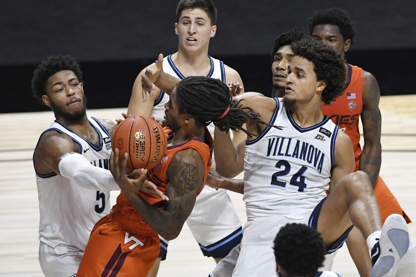 Virginia Tech's Cartier Diarra is fouled by Villanova's Justin Moore, left, as Villanova's Jeremiah Robinson-Earl, right, defends during the second half of an NCAA college basketball game Saturday, Nov. 28, 2020, in Uncasville, Conn. (AP Photo/Jessica Hill)
