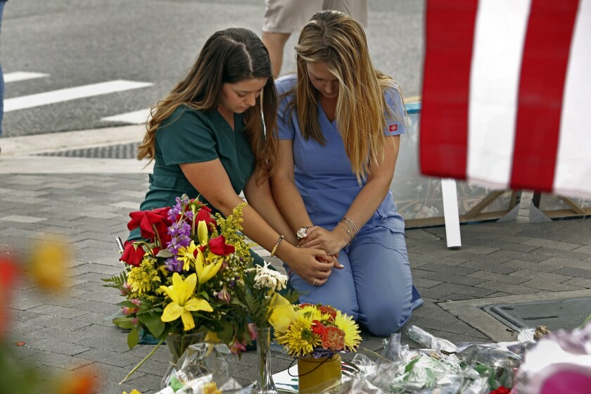Sarah Roemer, left, and Brandi Van Dongen, both nurses at Arnold Palmer Children's Hospital in Orlando, Fla., pray at one of the memorials to the victims of the Pulse nightclub shooting.