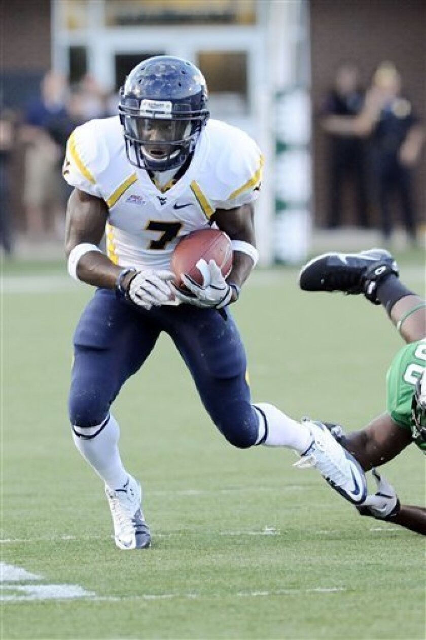 West Virginia's Noel Devine breaks the tackle of Marshall's Mario Harvey during the first quarter of a NCAA football game Friday Sept. 10, 2010 in Huntington, W.Va. (AP Photo/Jeff Gentner)
