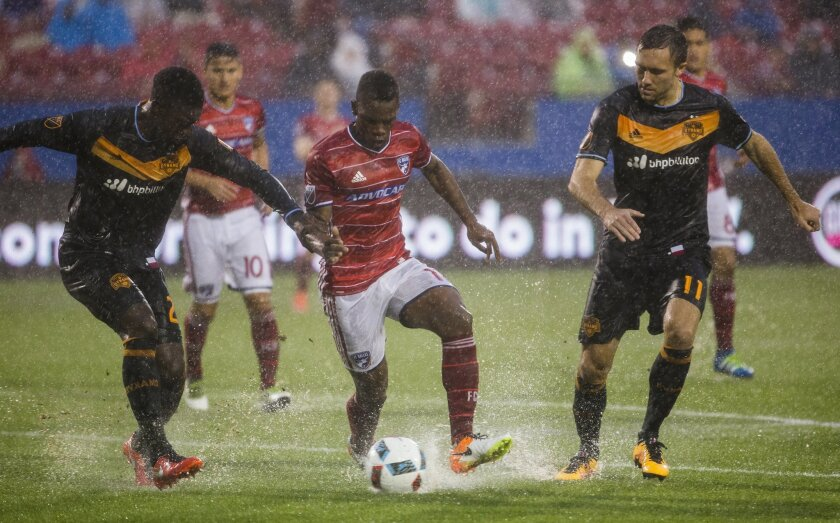 FC Dallas forward Fabian Castillo (11) controls the ball ahead of Houston Dynamo defender Jalil Anibaba (2) and Houston Dynamo forward Andrew Wenger (11) during the first half of a MLS soccer game on Thursday, June 2, 2016, in Frisco, Texas.  (Ashley Landis/The Dallas Morning News via AP) MANDATORY