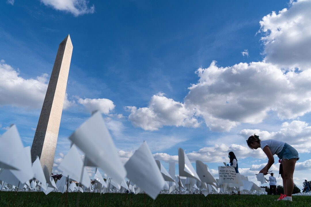 A woman bends over to place a small white flag in the grass, near the Washington Monument