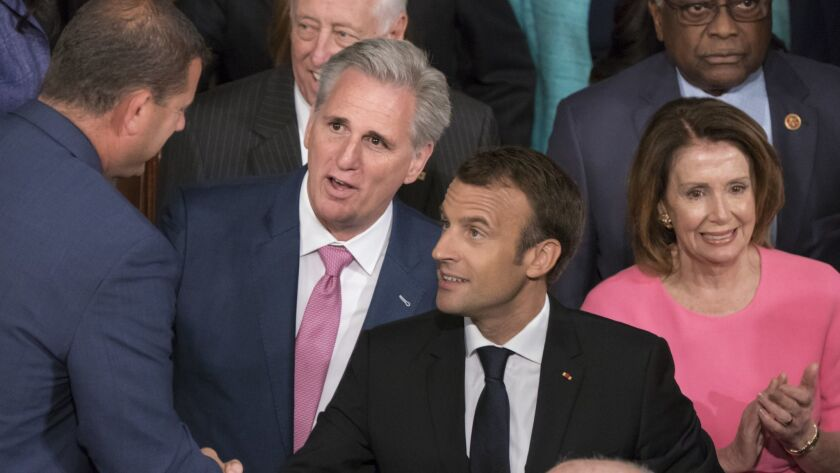 Congressional leaders Kevin McCarthy, second from left, and Nancy Pelosi, accompanying French President Emmanuel Macron, center, as he prepares to address Congress, represent vastly different constituencies.