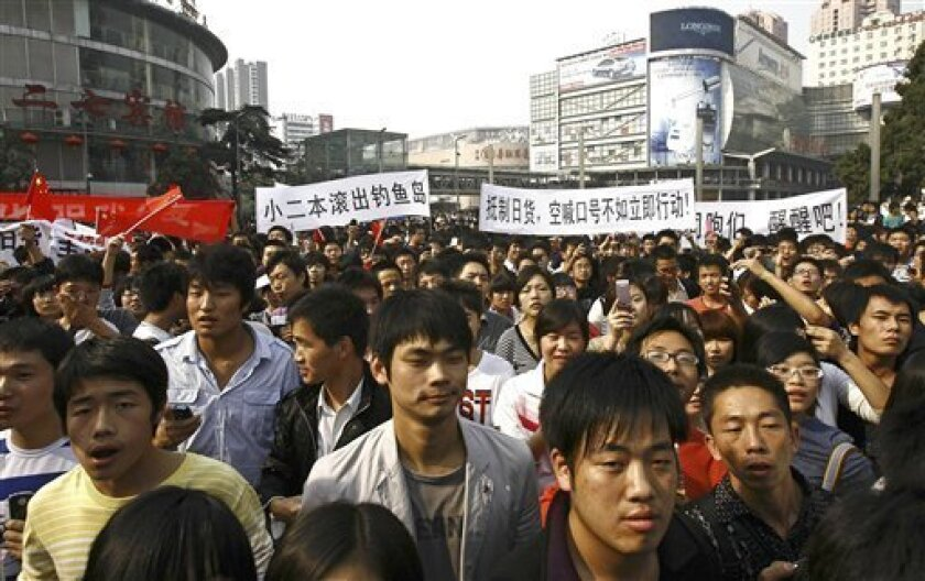 """People march during an anti-Japan protest in downtown Zhengzhou, in central China's Henan province, Saturday, Oct. 16, 2010. Chinese characters on the banners read, """"Boycott Japanese Products,"""" and """"Japanese, Get Out Of Diaoyu Island.""""(AP Photo)"""