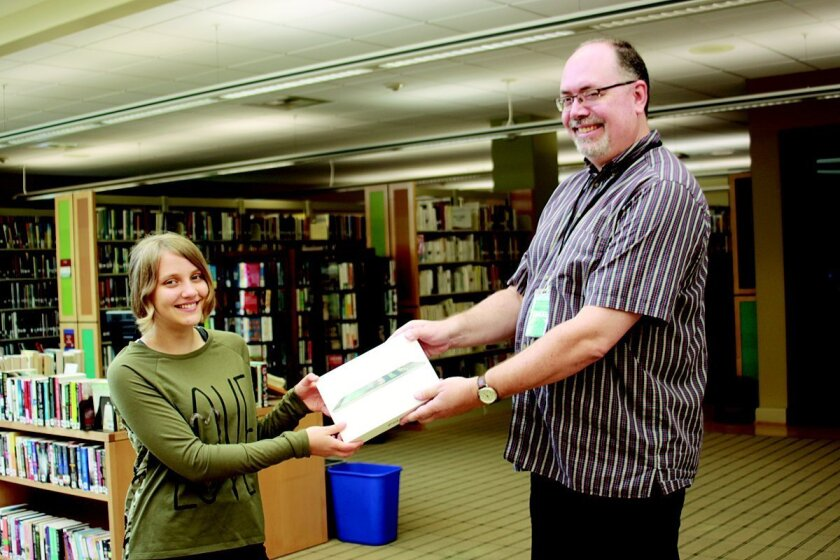 La Jolla Youth Librarian Bill Mallory presents 13-year-old Belisha Genin with an iPad, which she won through the summer reading program.
