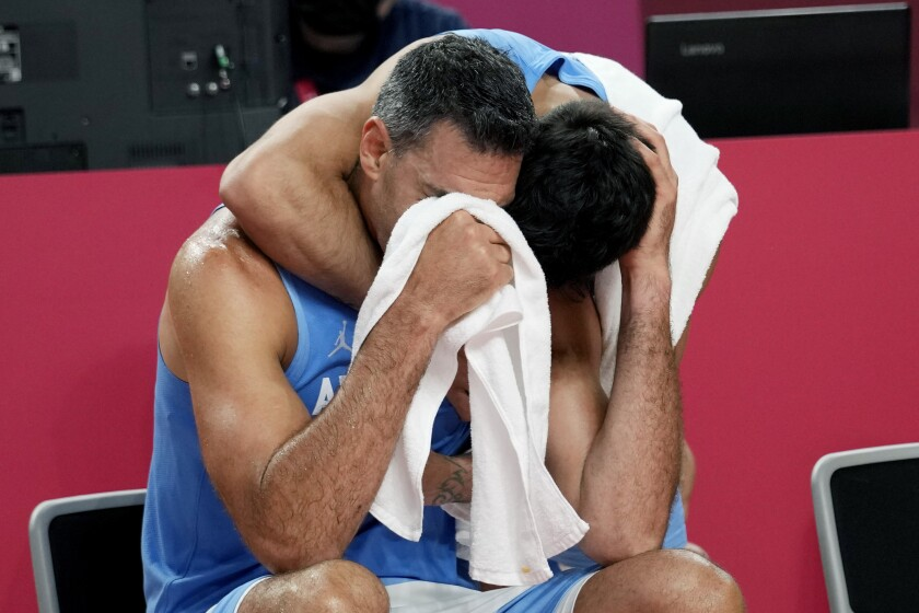Argentina's Luis Scola (4) is hugged by teammate Facundo Campazzo as he receives an emotional standing