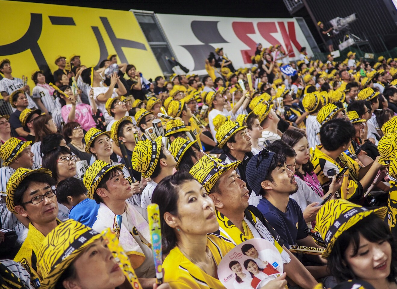 OSAKA, JAPAN - A lively outfield crowd, clad in tiger-striped fedoras, cheers on the Osaka-based Hanshin Tigers. Nippon Professional Baseball games are typically sold out, with lively crowds paying close attention to the action on the field.