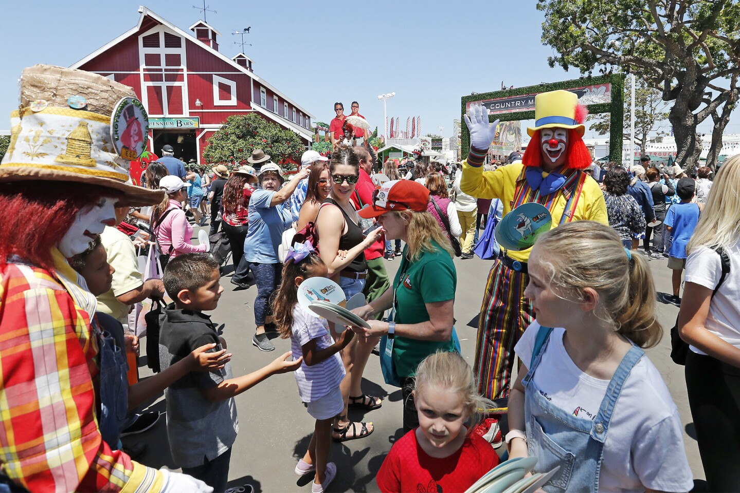 Fair clowns greet visitors at the Blue Gate entrance on opening day of the Orange County Fair on Friday in Costa Mesa.
