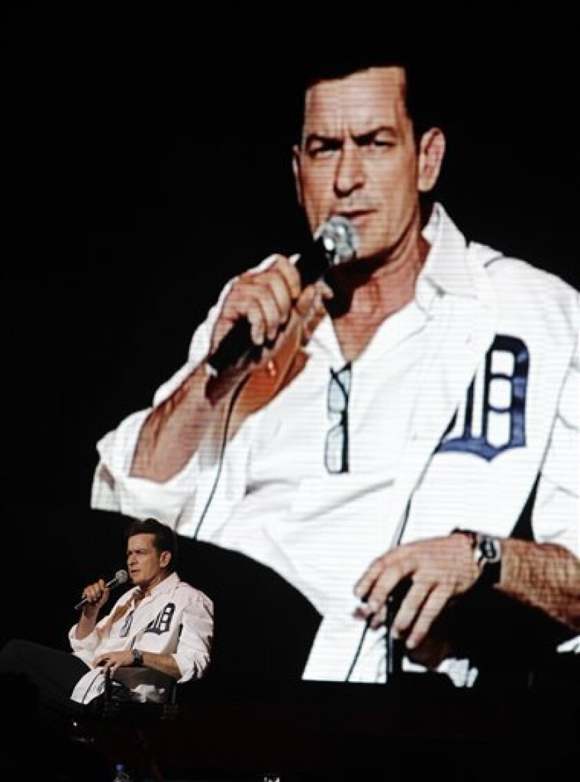 "An image of Charlie Sheen is projected in the background as he performs at the Fox Theatre in Detroit, Saturday, April 2, 2011. Promising ""the real story,"" the 45-year-old former ""Two and a Half Men"" star hit the road for a month-long, 20-city variety show tour, with the first stop Saturday's sold-out show in Detroit. (AP Photo/Carlos Osorio)"