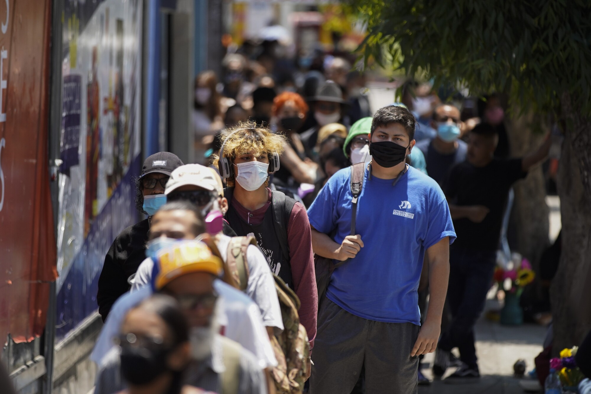 Mask-wearing people wait in a long line outside at the San Ysidro Port of Entry to cross from Tijuana