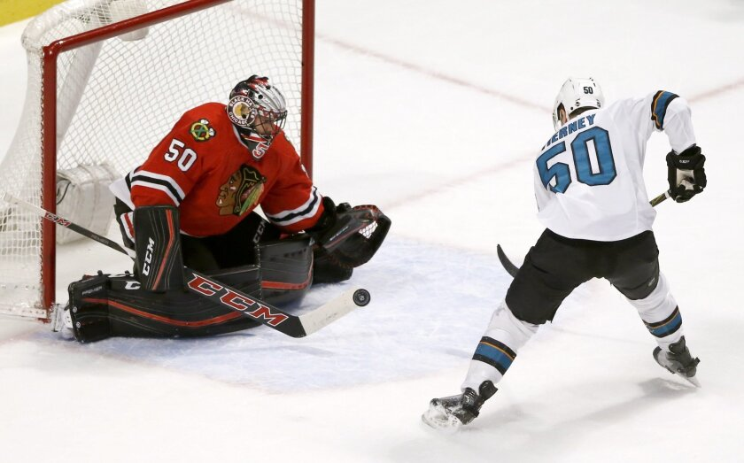 Chicago Blackhawks goalie Corey Crawford, left, makes a save on a shot by San Jose Sharks center Chris Tierney (50) during the second period of an NHL hockey game Tuesday, Feb. 9, 2016, in Chicago. (AP Photo/Charles Rex Arbogast)