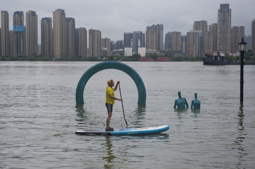 A man paddles by a sculpture submerged by floodwaters along the riverside park in Wuhan in central China's Hubei province Sunday, July 5, 2020. A wide swath of southern China braced Sunday for more seasonal rains and flooding that state media said has already left more than 120 people dead or missing this year. (Chinatopix via AP)