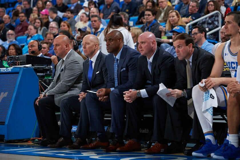 UCLA men's basketball coaches sit on the bench during a recent game.