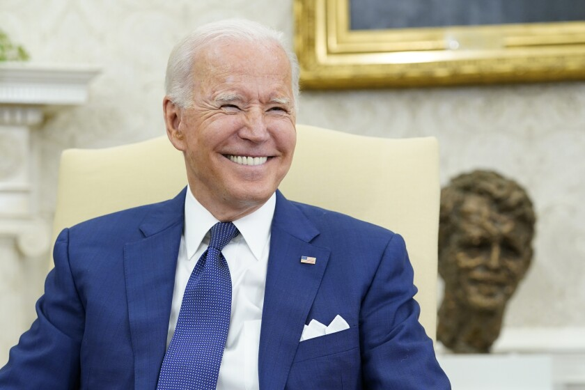 President Biden smiles during a meeting in the Oval Office.