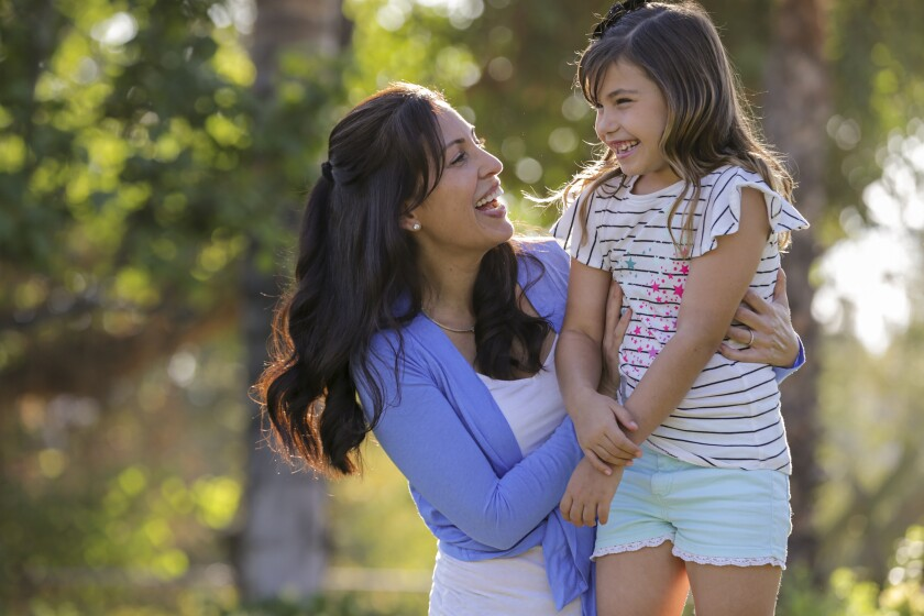 A woman and her daughter laugh and embrace outside