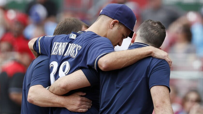Milwaukee Brewers relief pitcher Dan Jennings is helped off the field after suffering an injury against the Cincinnati Reds on Aug. 30.