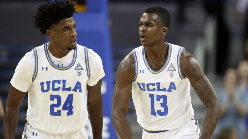 UCLA guard Kris Wilkes, right, celebrates after dunking the ball along with guard Jalen Hill, left,