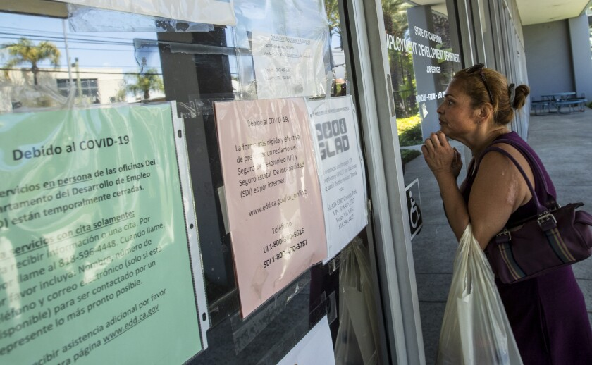 A woman looks through the glass front door of the closed California Employment Development Department office in Canoga Park